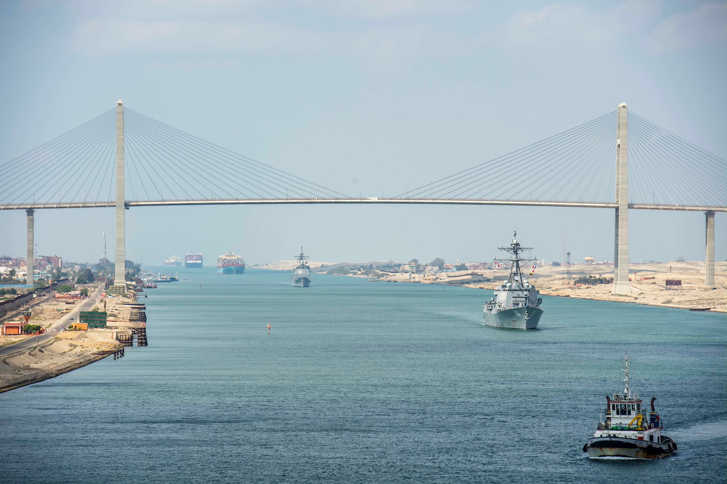 The guided-missile cruiser USS Monterey and the guided-missile destroyer USS Thomas Hudner are seen behind a tug following the aircraft carrier USS Dwight D Eisenhower during a transit of the Suez Canal on Friday. (US Navy Han