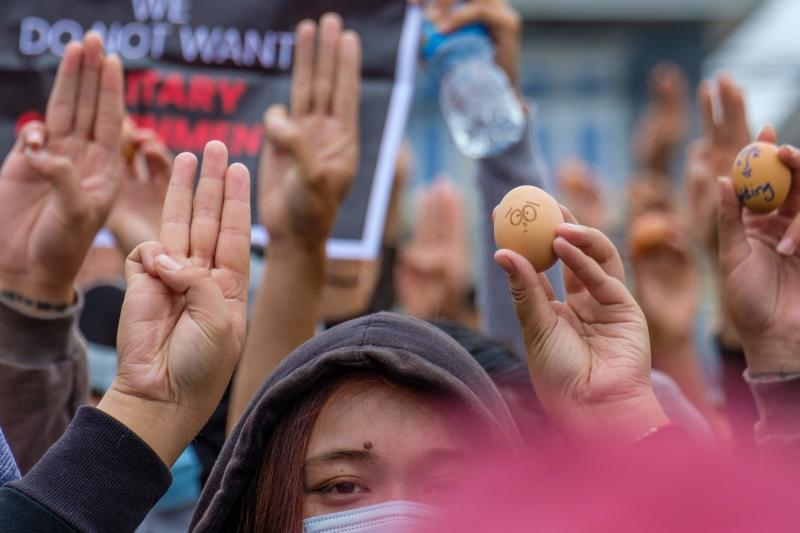 This photo taken and received courtesy of an anonymous source on Sunday shows protesters holding up eggs to coincide with Easter Sunday and making the three-finger salute during a demonstration against the military coup in Taunggyi in Myanmar's Shan state. (Photo by Handout / ANONYMOUS / AFP)