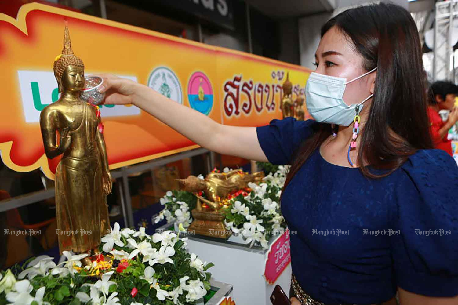 A woman bathes a Buddha image during an event to promote Songkran traditions in Bangkok late last month. (Photo: Somchai Poomlard)