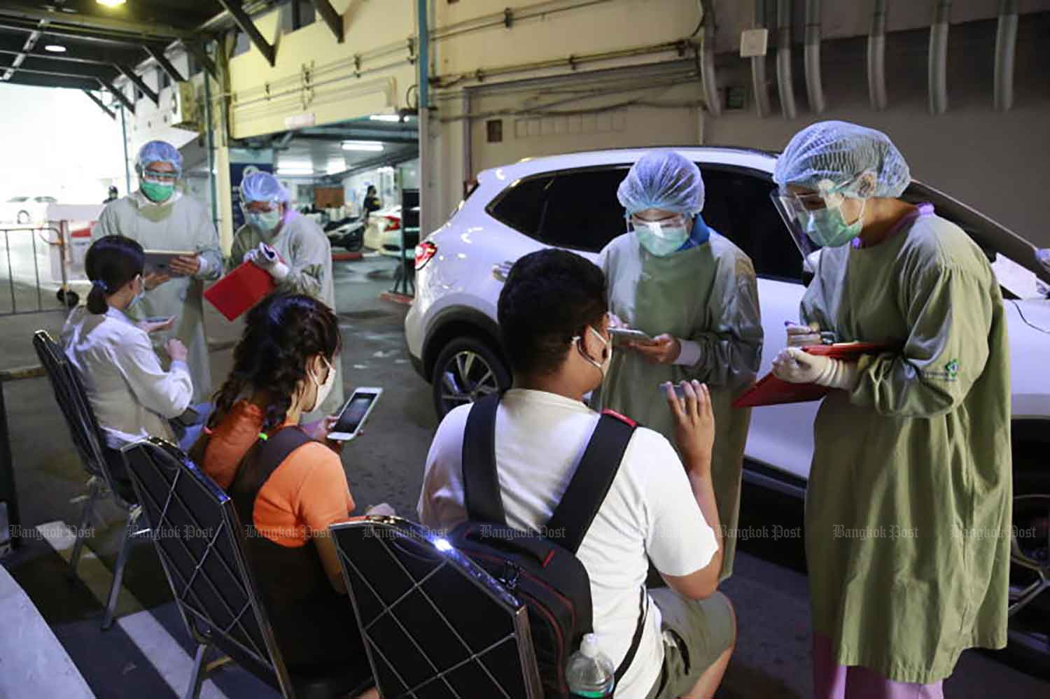 People wait to give samples at a drive-through Covid-19 testing unit at Vibhavadi Hospital in Bangkok on Tuesday, when the country logged 334 new cases. (Photo: Arnun Chonmahatrakool)
