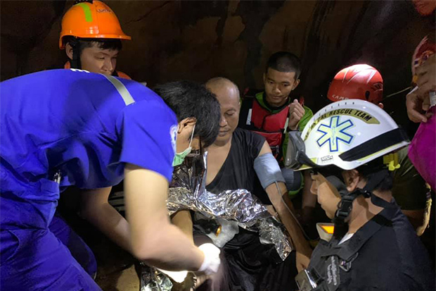 Rescue workers give Phra Ajarn Manas (seated, centre) first aid before bringing him safely out of Phra Sai Ngam Cave in Noen Maprang district of Phitsanulok on Wednesday. (Photo: Prasat Bun Sathan Rescue Foundation Facebook account)