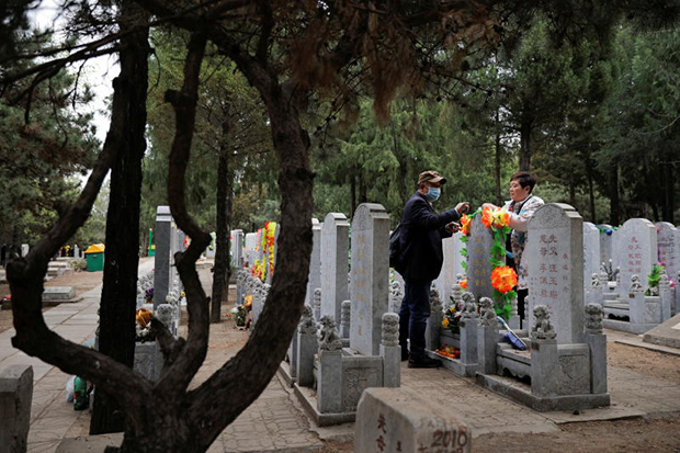People decorate a grave on the Tomb Sweeping Day, or Ching Ming Festival, at a graveyard in Beijing on Monday. (Reuters photo)