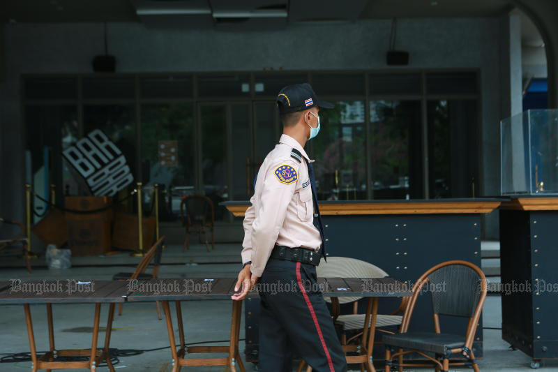 A security guard walks past a shuttered bar in Thong Lor area of Bangkok, the centre of a rapidly spreading new cluster of Covid-19. (Photo: Somchai Poomlard)