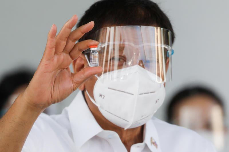 Philippine President Rodrigo Duterte holds a vial of Sinovac, the first Covid-19 vaccine to arrive in the country, at Villamor Air Base in Pasay City, Metro Manila, on Feb 28, 2021. (Reuters photo)