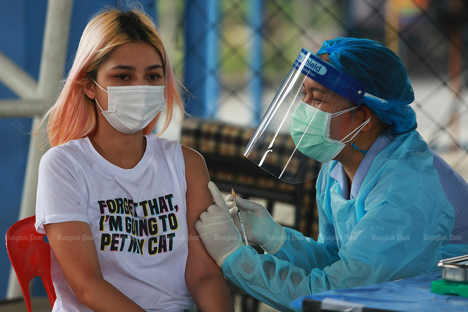 A resident of Watthana district in Bangkok is on Wednesday injected with vaccine against Covid-19 at the Sang Thip sports complex on Soi Pridi Banomyong 2 as she is considered as being in an at-risk group after a new cluster of Covid-19 from bars and pubs in the Thong Lor area emerged. (Photo by Somchai Poomlard)