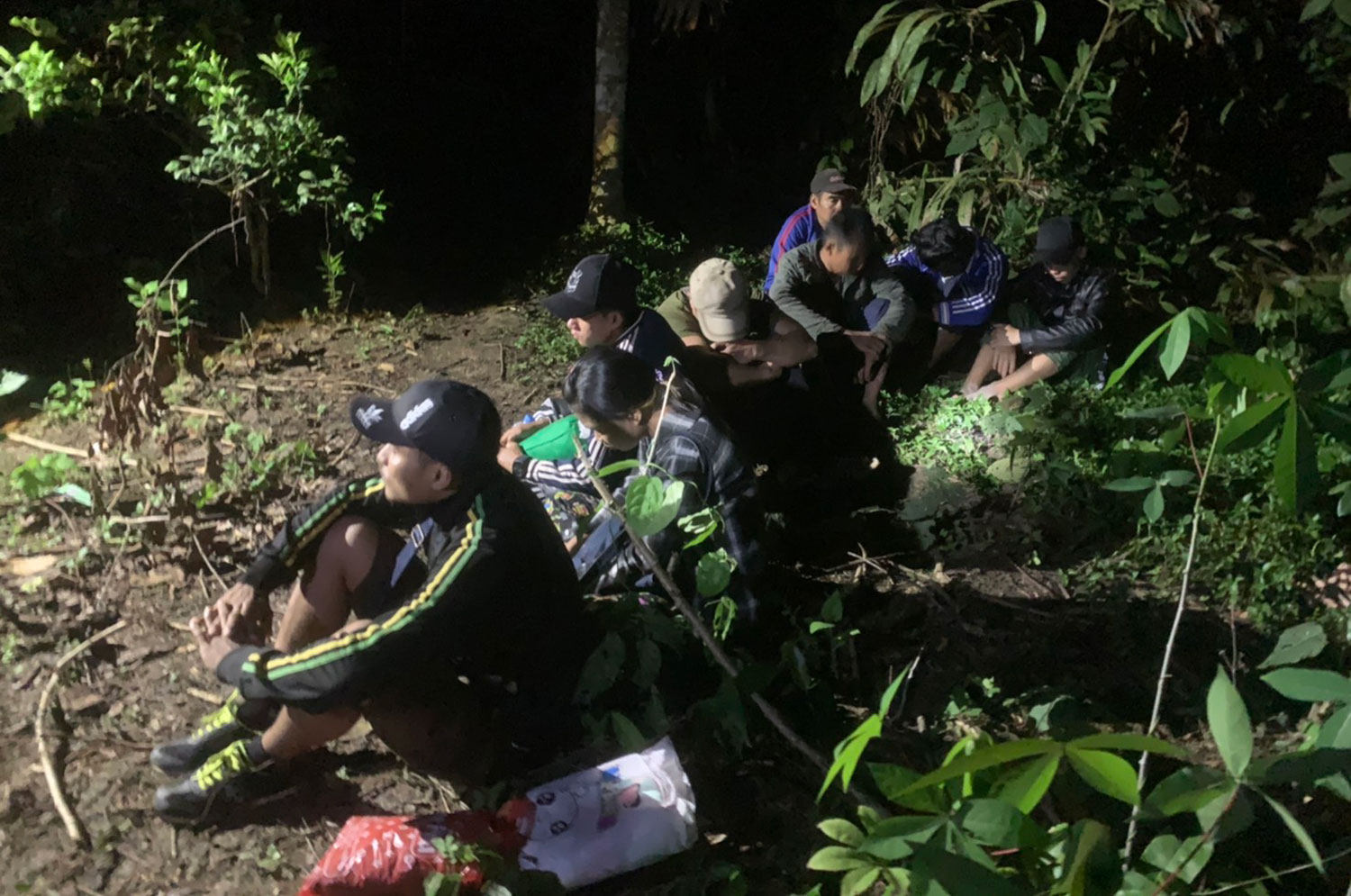 Eight Myanmar nationals are found in a forest near a pomelo planation in Sangkhla Buri district, Kanchanaburi, on Wednesday night. They said 20 job seekers had crossed the border together along a natural path, and 12 had already been taken away by job agents. (Photo: Piyarat Chongcharoen)
