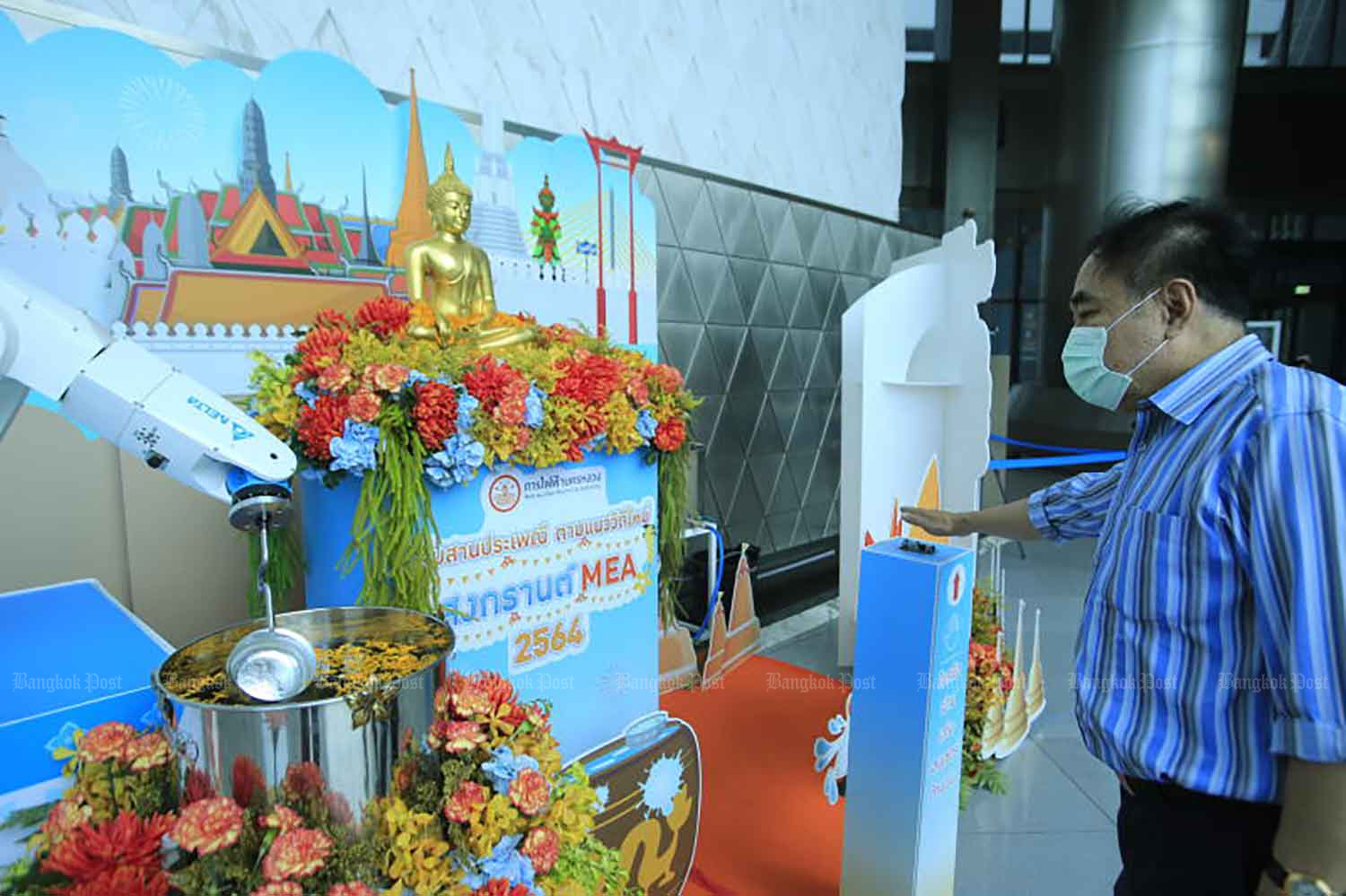 A man bathes a Buddha image using a robotic arm, to help limit the spread of Covid-19, at the Metropolitan Electricity Authority building in Klong Toey district, Bangkok, on Thursday, when the country logged 559 new cases. (Photo: Pornprom Satrabhaya)