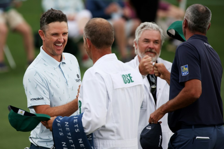 England's Justin Rose, left, bumps fists with caddie David Clark after firing a seven-under par 65 in Thursday's opening round of the Masters.