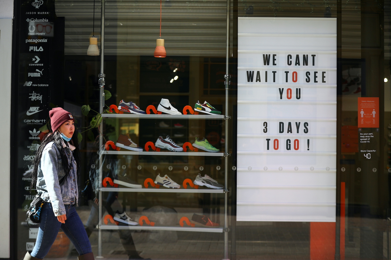 A pedestrian walks by a store being prepared for reopening in London on Friday. (Reuters Photo)