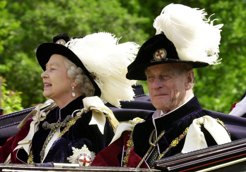 Britain's Queen Elizabeth II and Prince Phillip, the Duke of Edinburgh, wearing their Order of the Garter robes, ride in an open-topped carriage to Windsor Castle following the Garter Ceremony, June 18, 2001. (Reuters photo)