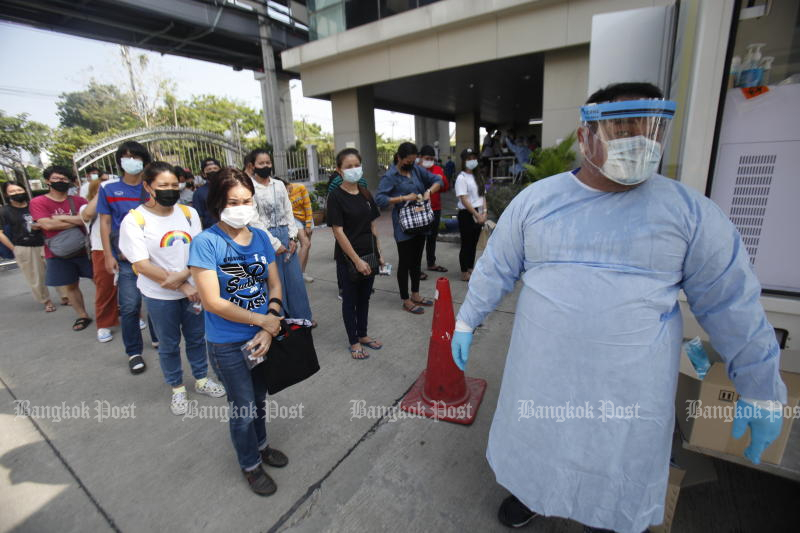 People wait their turn to give a nasal swab, for testing for the Covid-19 virus, at the office of the Department of Disease Control in Bang Khen district, Bangkok, on Wednesday. (Photo: Nutthawat Wicheanbut)