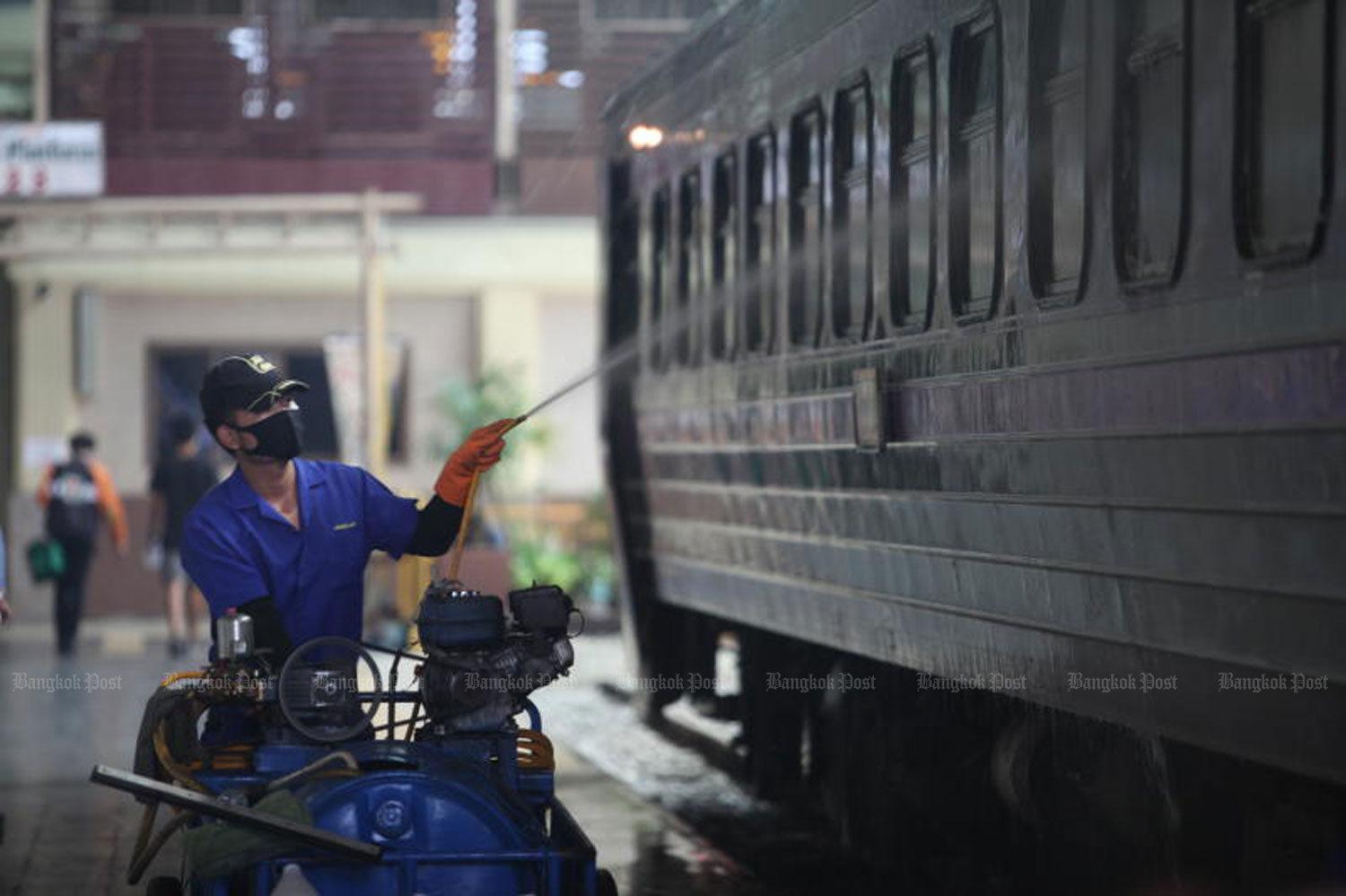 A man cleans a train carriage at Hua Lamphong railway station on Friday. Songkran travellers are returning from the provinces to Bangkok after the long holiday officially ended on Thursday. (Photo by Apichart Jinakul)