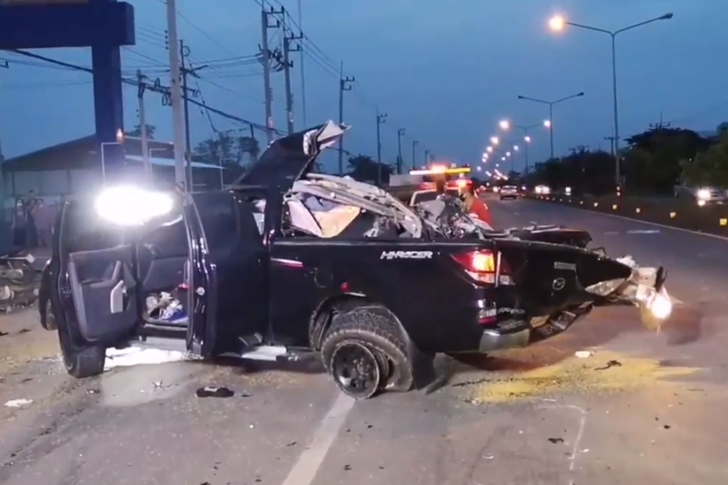 The wreckage of a pickup truck hit by a six-wheel lorry from the opposite lane on Warin-Katharalak Road in Warin Chamrap, Ubon Ratchathani, on Friday evening. A nine-year-old girl and her father, 29, in the pickup truck were killed while the mother, also 29, was sent to a hospital. The driver of the lorry, who was slightly hurt, was drunk. (Image from a video supplied by Dusit Singkhiri)