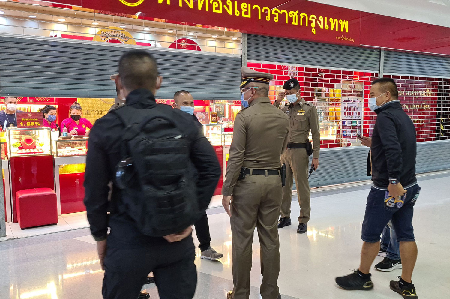 Police question a staffer of the gold shop at the Big C Khlong Hae mall in Hat Yai following a robbery on Saturday afternoon. (Photo: Assawin Pakkawan)