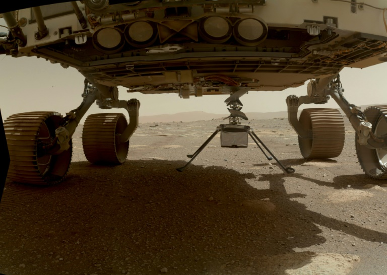 NASA's Ingenuity Mars Helicopter, with all four of its legs deployed, is pictured before dropping from the belly of the Perseverance rover in March 2021.