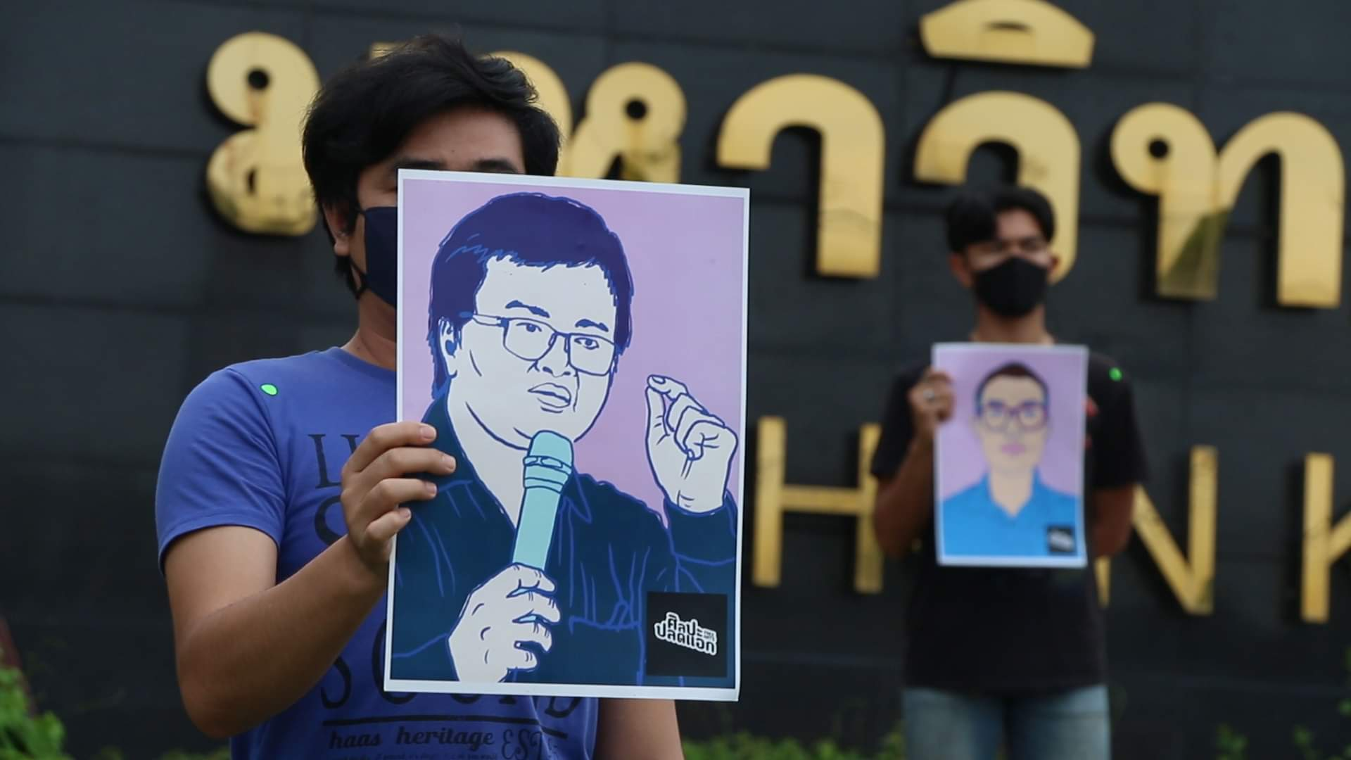 A protester shows a picture of Parit Chiwarak during he silenbt protest against the detention of leading activists, outside Khon Kaen University on Sunday. (Photo:  Chakkrapan Natanri)