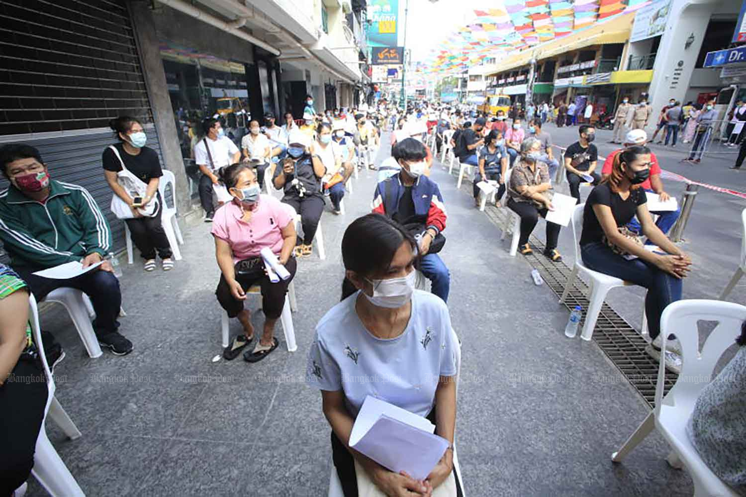 People wait for their turn to be tested for Covid-19 behind a royally-donated mobile medical unit that is stationed at Khao San Road in Bangkok on Monday. (Photo: Pornprom Satrabhaya)
