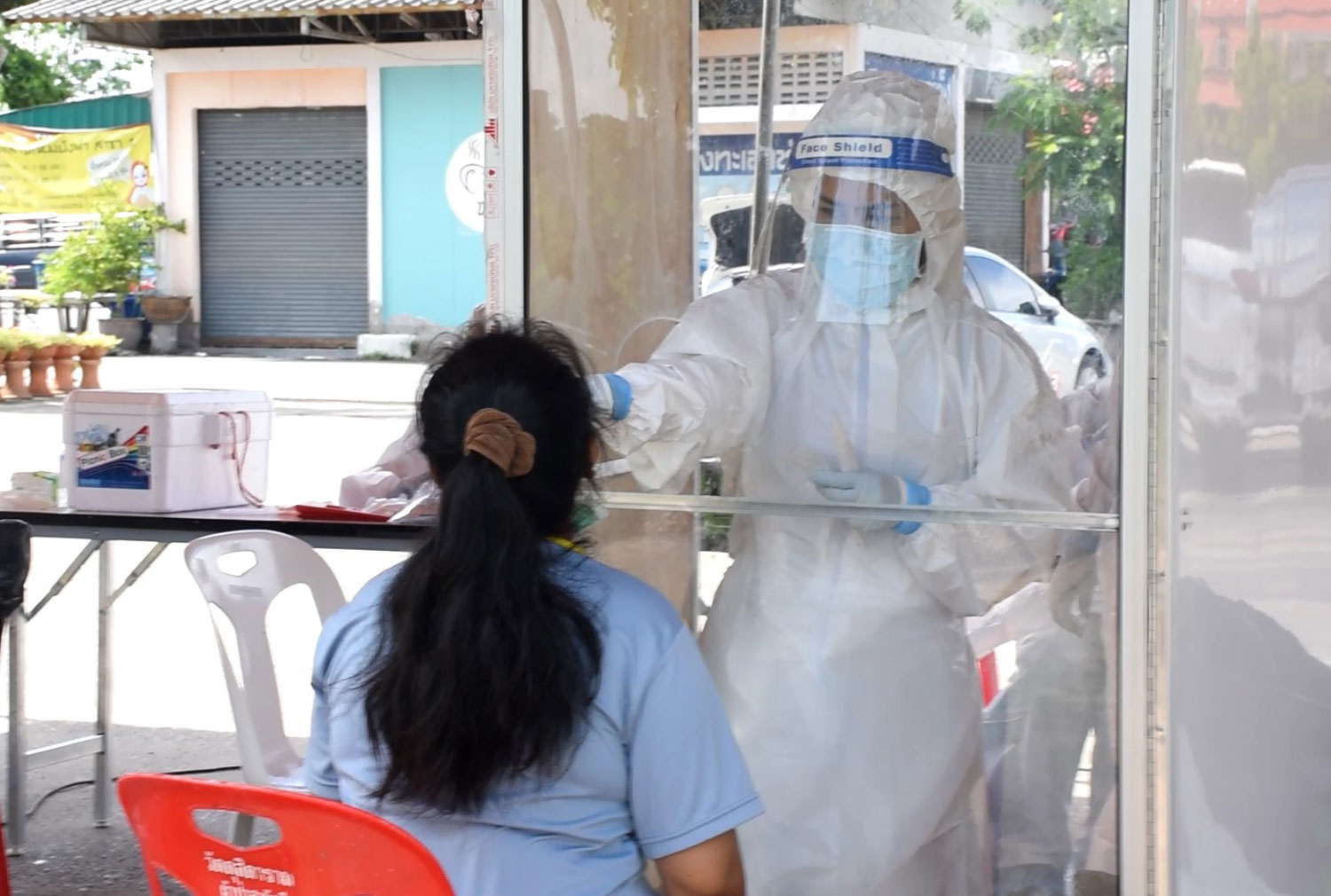 A health official collects a nasal swab from a woman in Ayutthaya province on Tuesday, when the central province reported 14 more Covid-19 cases. (Photo: Sunthon Pongpao)
