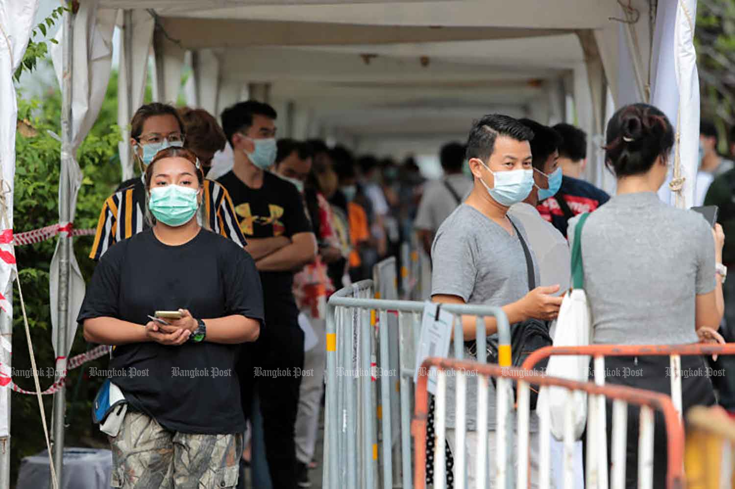 Social Security Fund members wait for free Covid-19 testing at the Bangkok Youth Centre in Din Daeng district on Wednesday. (Photo: Chanat Katanyu)