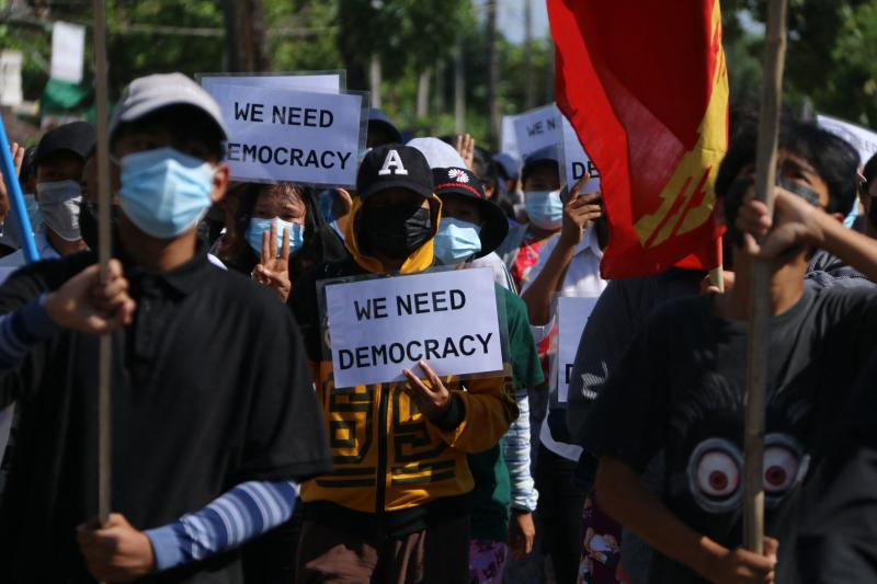 Protesters hold signs as they march in a demonstration against the military coup in Dawei on Tuesday. (AFP PHOTO / DAWEI WATCH)
