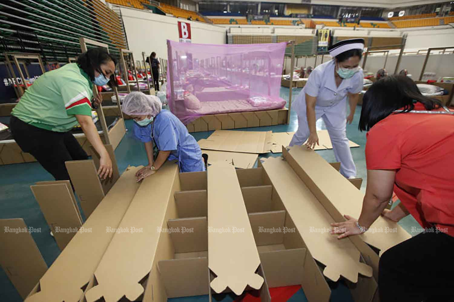 Health workers assemble cardboard-frame beds at Bangkok Arena, which is being used as a field hospital for Covid-19 patients, in Nong Chok district on Wednesday, when the country logged seven new deaths related to the virus and 1,470 new cases.(Photo: Varuth Hirunyatheb)