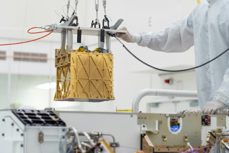 This handout photo obtained April 21, 2021 and released by NASA/JPL shows technicians in the clean room carefully lowering the Mars Oxygen In-Situ Resource Utilization Experiment (MOXIE) instrument into the belly of the Perseverance rover