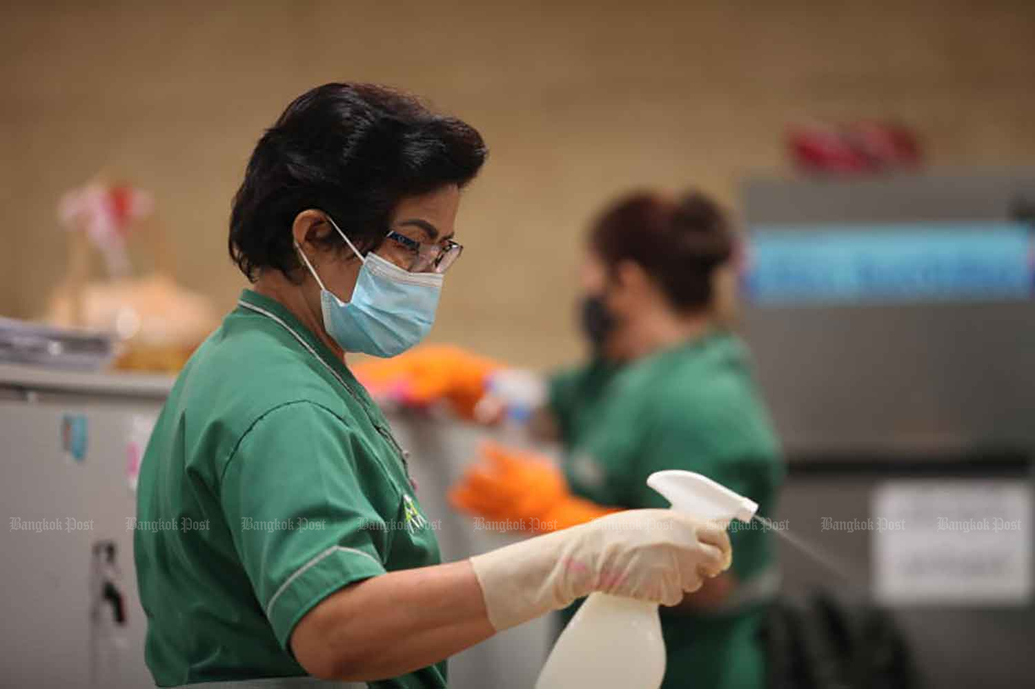 Workers disinfect the media room at the parliament complex in Bangkok on Friday, when the country posted a new high of 2,070 Covid-19 cases in one day, together with four deaths. (Photo: Apichart Jinakul)