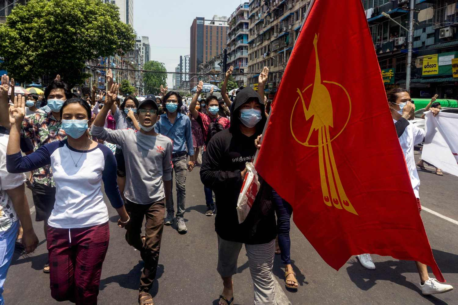 A protester holds the Myanmar Student Union flag as others make the three-finger salute during a demonstration against the military coup in Yangon on Friday. (Photo by Stringer via AFP)