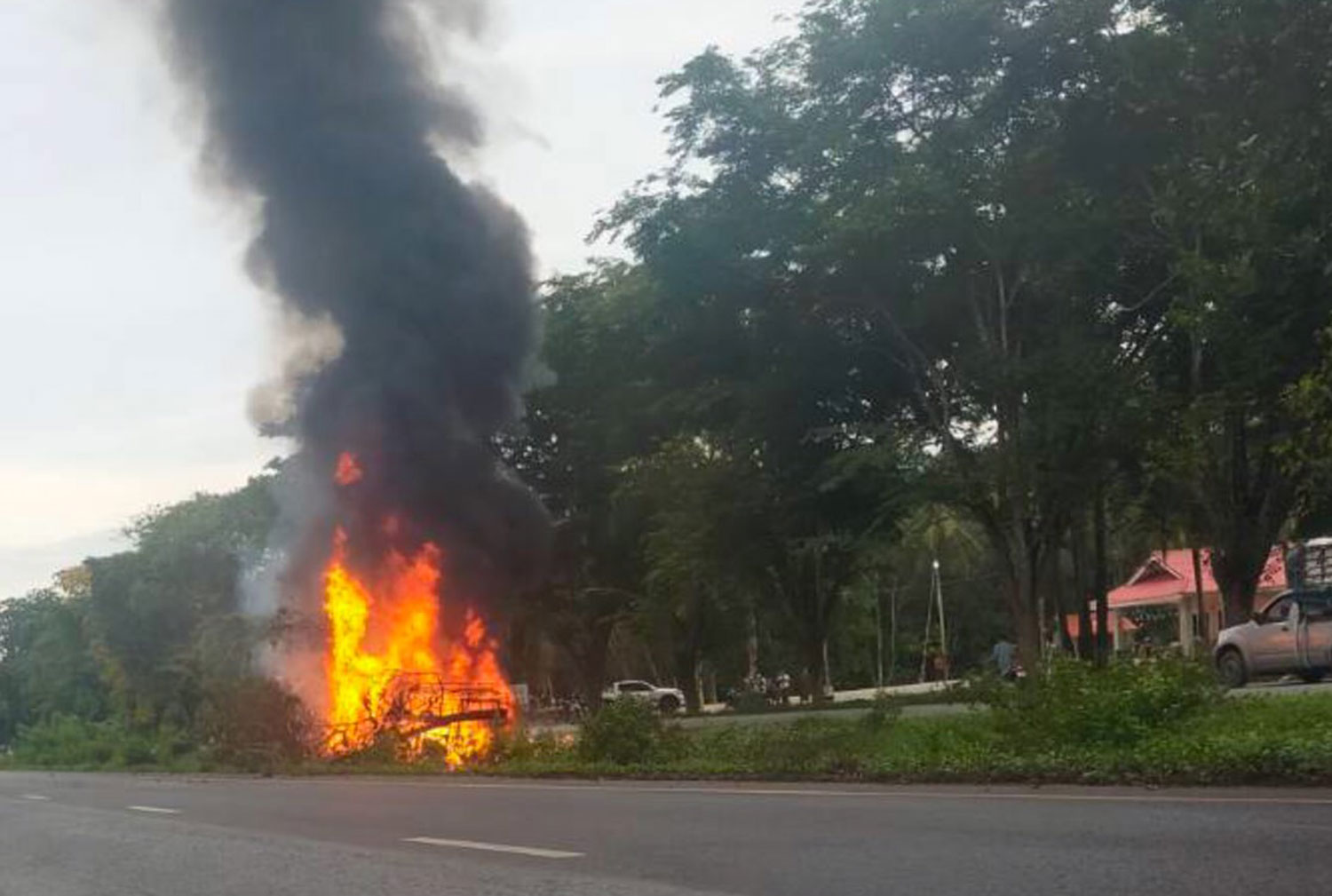 Flames rise from two pickup trucks on a road in Sai Buri district of Pattani after assailants opened fire on Saturday morning, killing three people inside the vehicles. (Photo: Abdullah Benjakat)