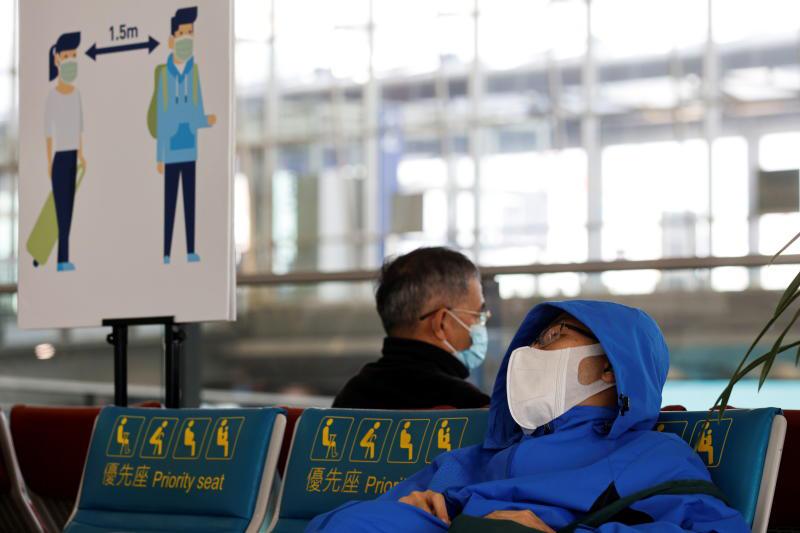 People wear face masks, following the coronavirus outbreak, at Hong Kong International Airport in Hong Kong on Feb 2, 2021. (Reuters photo)