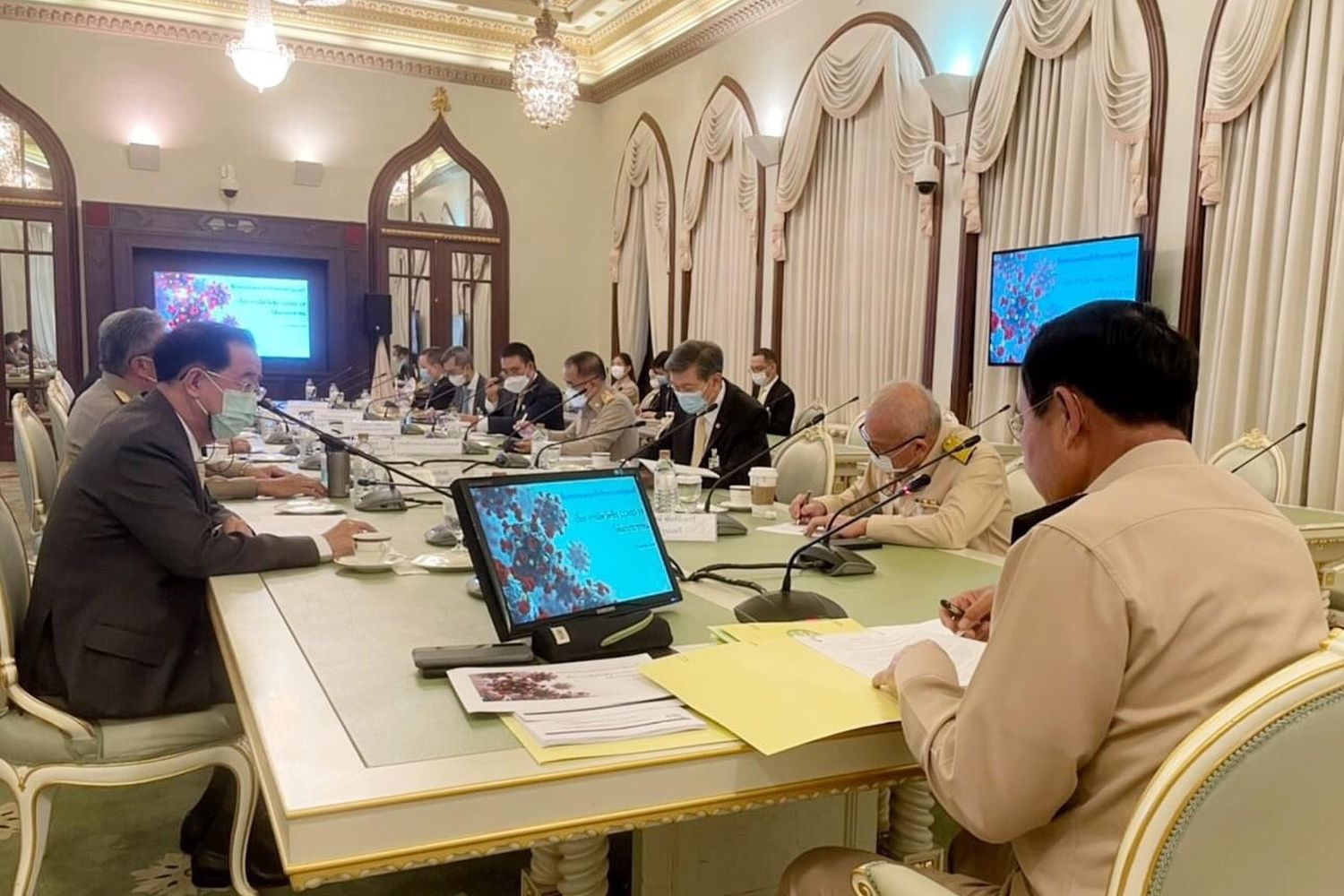 Prime Minister Prayut Chan-o-cha (right) chairs a meeting on Covid-19 vaccine procurement at Government House on Monday. Criticism followed that he failed to wear a mask and the photo was removed from Facebook. (Government House photo)