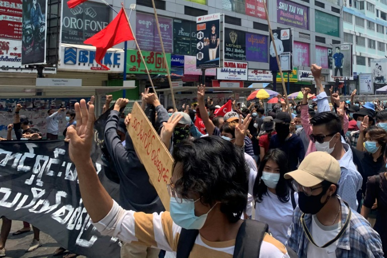 Protesters hold up the three finger salute as they take part in a demonstration against the military coup in Tarmwe township in Yangon on Monday.