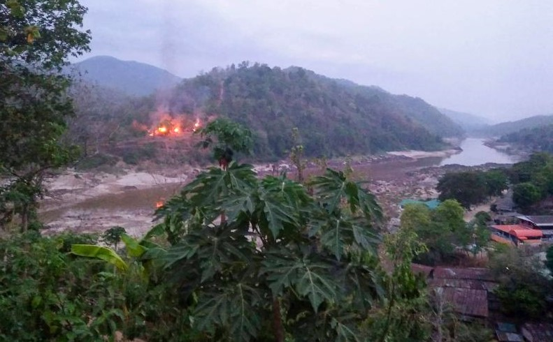 This handout from Kawthoolei Today taken and released on April 27, 2021 shows fires burning at a Myanmar military base along the bank of the Salween river, as seen from Mae Sam Laep town in Thailand's Mae Hong Son province, after the base was attacked and captured by the Karen National Union (KNU) as the country remains in turmoil after the Feb 1 military coup. (Photo by Handout / KAWTHOOLEI TODAY / AFP)