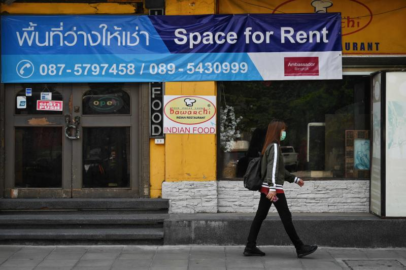 A woman walks past a closed-down restaurant in the once-popular tourist street Sukhumvit Soi 11 in Bangkok on April 16, 2021. (AFP file photo)
