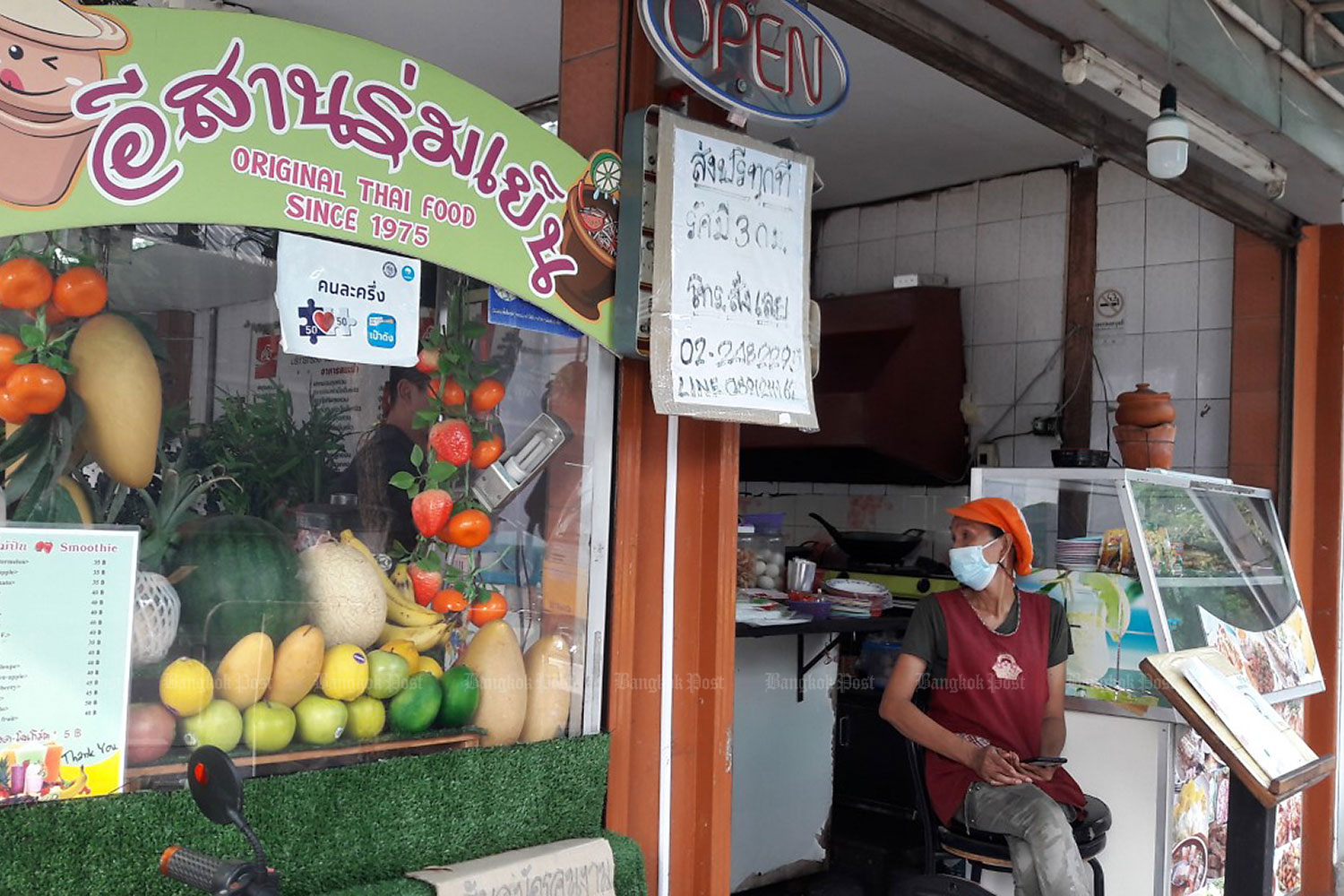 A cook sits outside her eatery in Soi Rang Nam in the capital. Business has plummeted in the wake of the outbreak of the third wave of Covid-19.