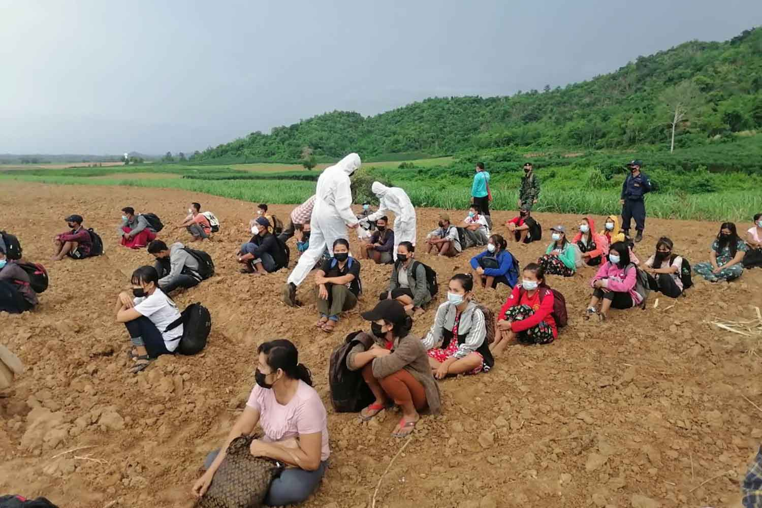 Myanmar migrants have their temperatures taken by two soldiers from the Lat Ya Task Force wearing PPE suits some of 60 illegal job seekers caught on Tuesday after crossing the border into Kanchanaburi province. (Photo: Piyarat Chongcharoen)