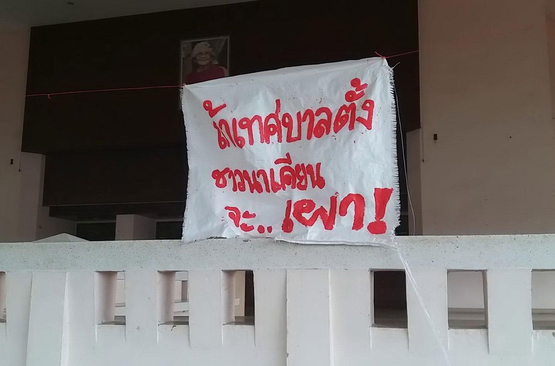 A cloth banner declares,