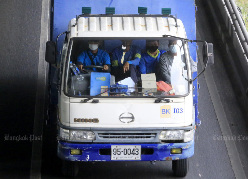 The driver and passengers in a lorry are seen wearing masks after mask-wearing was made compulsory in vehicles with at least one passenger. (Photo by Pornprom Satrabhaya)