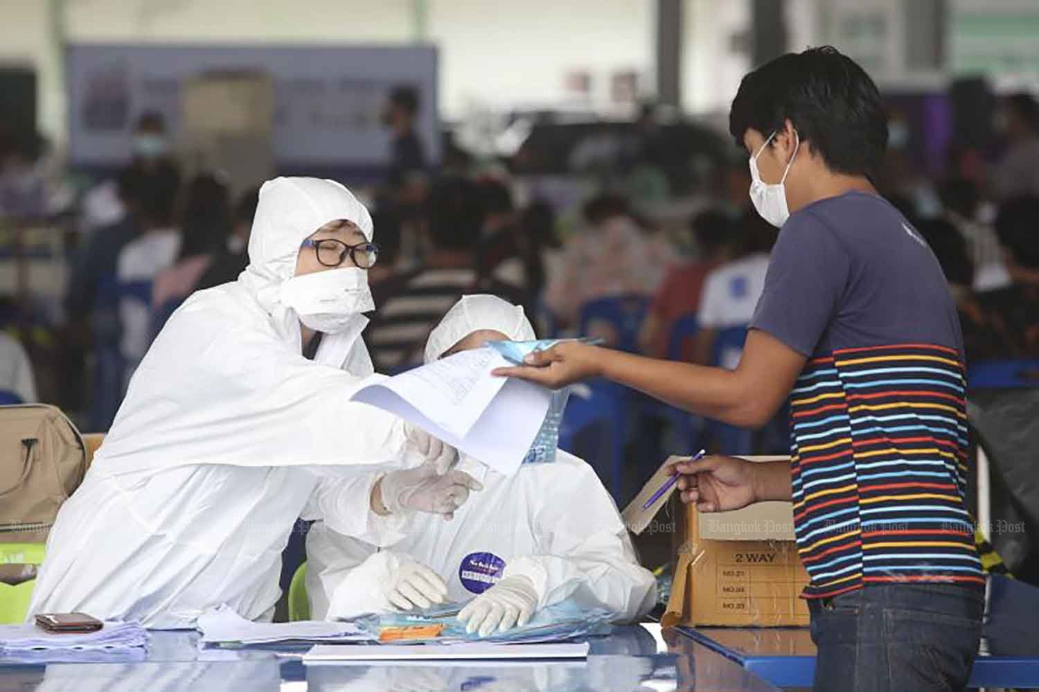 Health workers give free Covid-19 tests to social security fund members at Phimolrat municipal office in Bang Bua Thong district, Nonthaburi, on Thursday. (Photo: Pattarapong Chatpattarasill)