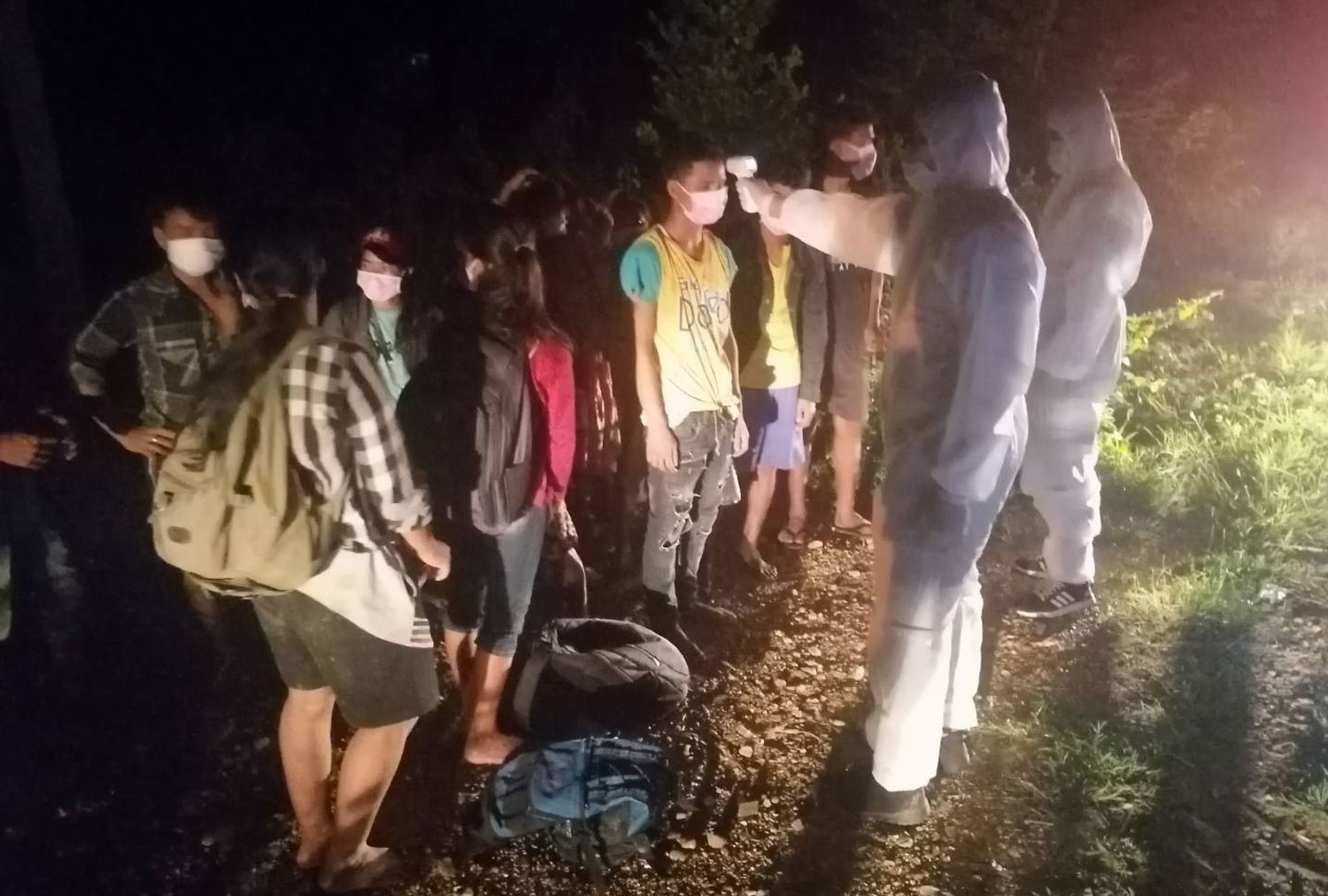Soldiers in PPE suits check the temperatures of Myanmar border crossers caught in Muang district, Kanchanaburi on Wednesday night.  (Photo: Piyarat Chongcharoen)