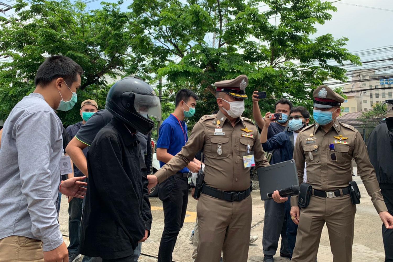 Phaiwan Aechaiyaphum, 48, wearing a full-face crash helmet, is taken for a re-enactment of his stone attacks in Bangkok, on Thursday. (Photo: Wassayos Ngamkham)