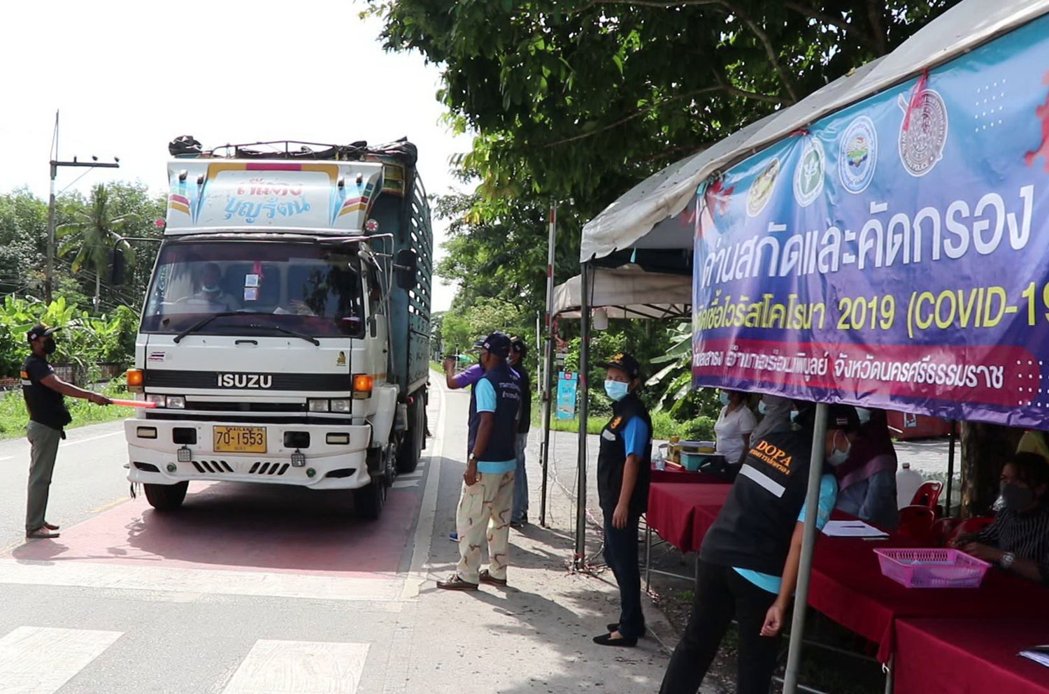 Officials at a Covid-19 screening checkpoint in tambon Sao Thong of Ron Phibun district on Friday stop a truck to inspect the people on board. (Photo: Nujaree Rakrun)