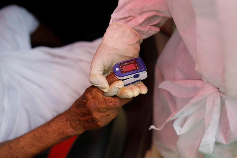 A volunteer uses an oximeter to check the oxygen level of a man amidst the spread of coronavirus disease outside a Sikh temple in Ghaziabad, India, on Friday. (Reuters photo)