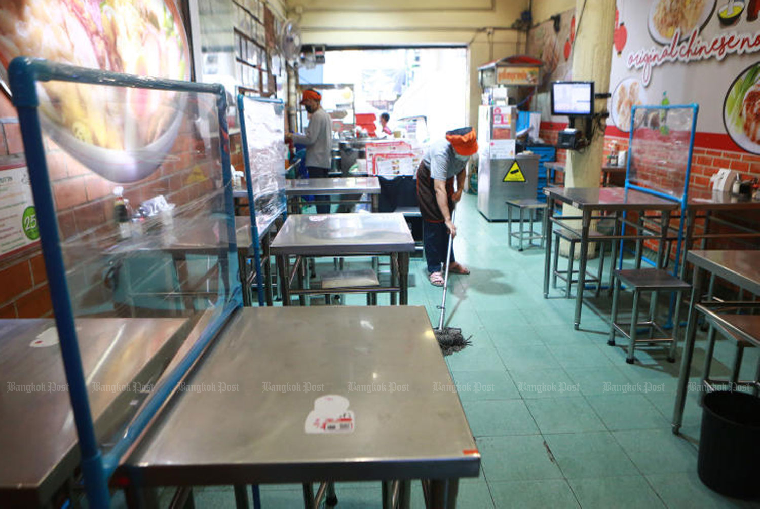 A woman cleans the floor of a food shop in Bangkok on Friday. Saturday is the first day no dining-in is allowed in the capital, as well as in other provinces in the dark red zone, as authorities step up efforts to contain the Covid-19 spread. Delivery and take-home orders are still allowed until 9pm. (Photo: Somchai Poomlard)