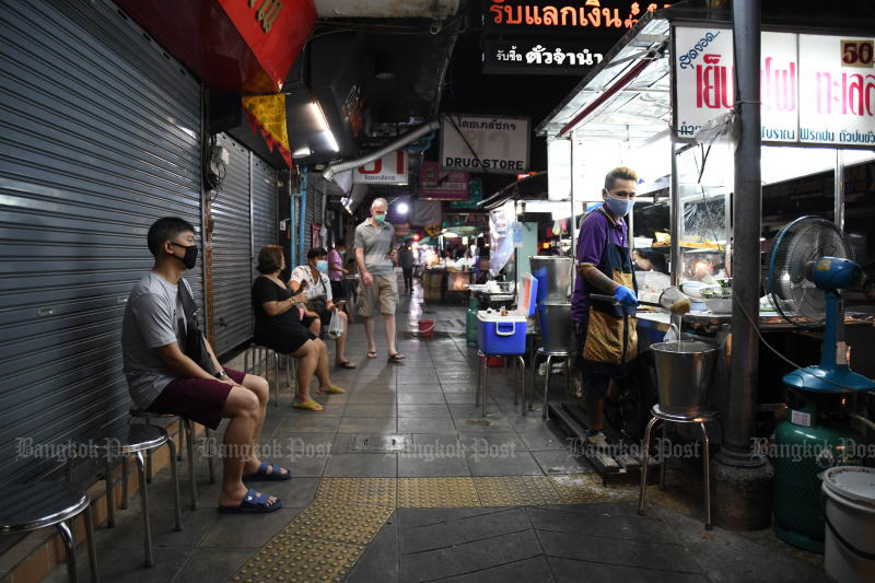 Customers wait for their noodle soup at a roadside shop on Padiphat Road in Bangkok on Saturday. (Photo by Nutthawat Wicheanbut)