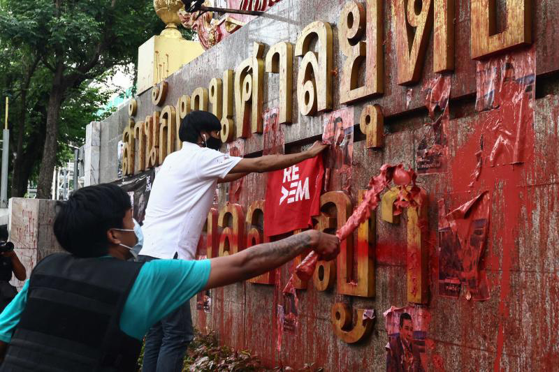 Pro-democracy protesters splash paint on the exterior of the Criminal Court premises during an anti-government demonstration calling for the release of detained political activists on Sunday. (AFP photo)