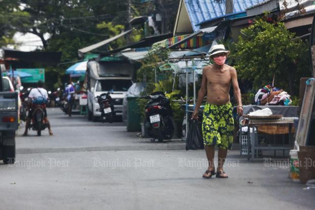 A man walks through 70-Rai community in Klong Toey district of Bangkok on Sunday. The community is the centre of a new Covid-19 cluster. (Photo: Arnun Chonmahatrakool)