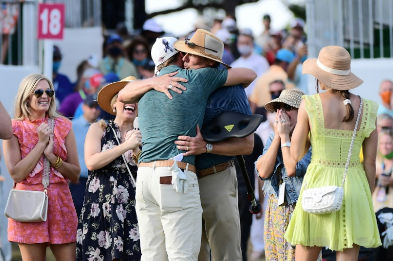 Sam Burns, his back to the camera, hugs his father as he celebrates with his family on the 18th green after winning his first US PGA title at the Valspar Championship.