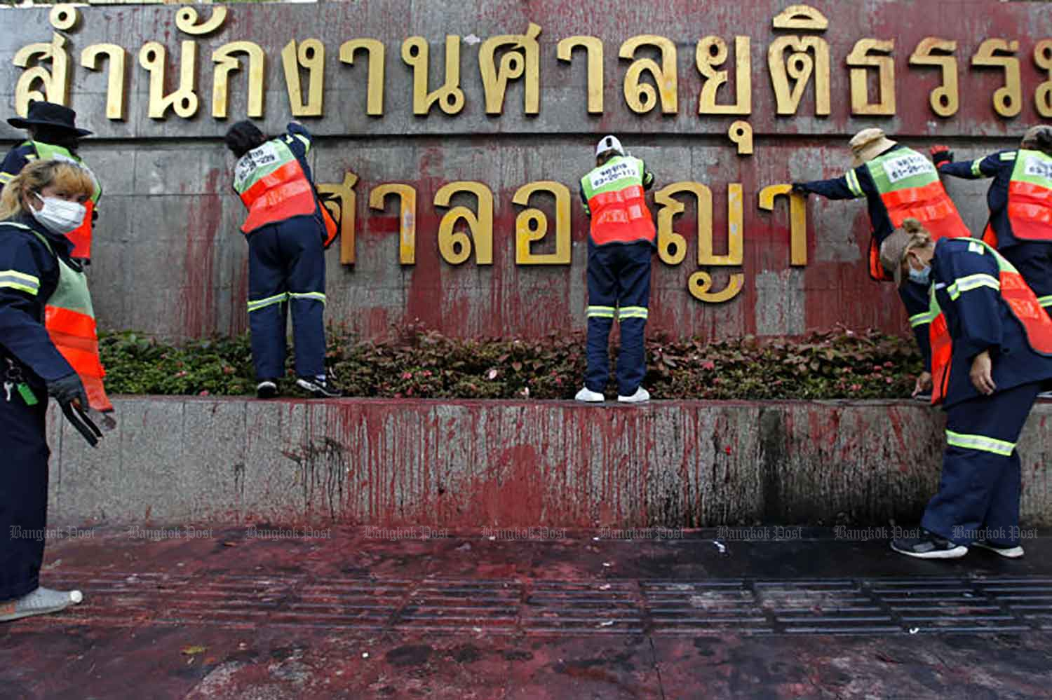 City workers are cleaning paint in front of the Criminal Court in Bangkok on Monday, after a protest there on Sunday when protesters splash red paint there. (Photo by Varuth Hirunyatheb)