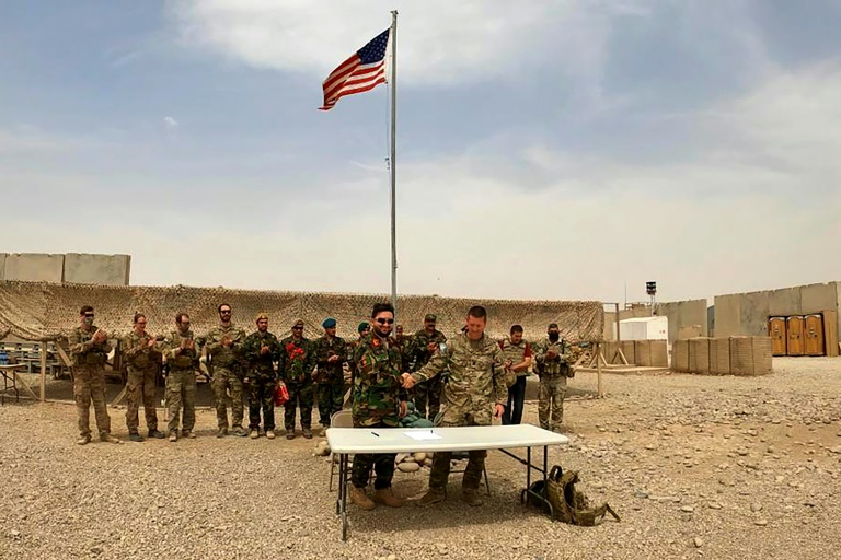 A US and Afghan soldier shake hands during the handover ceremony at Camp Antonik in Helmand province